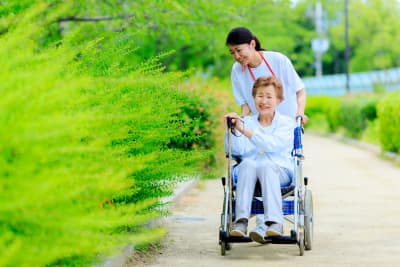 elderly woman on a wheelchair with her caregiver