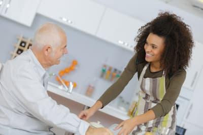 caregiver serving food to a senior man